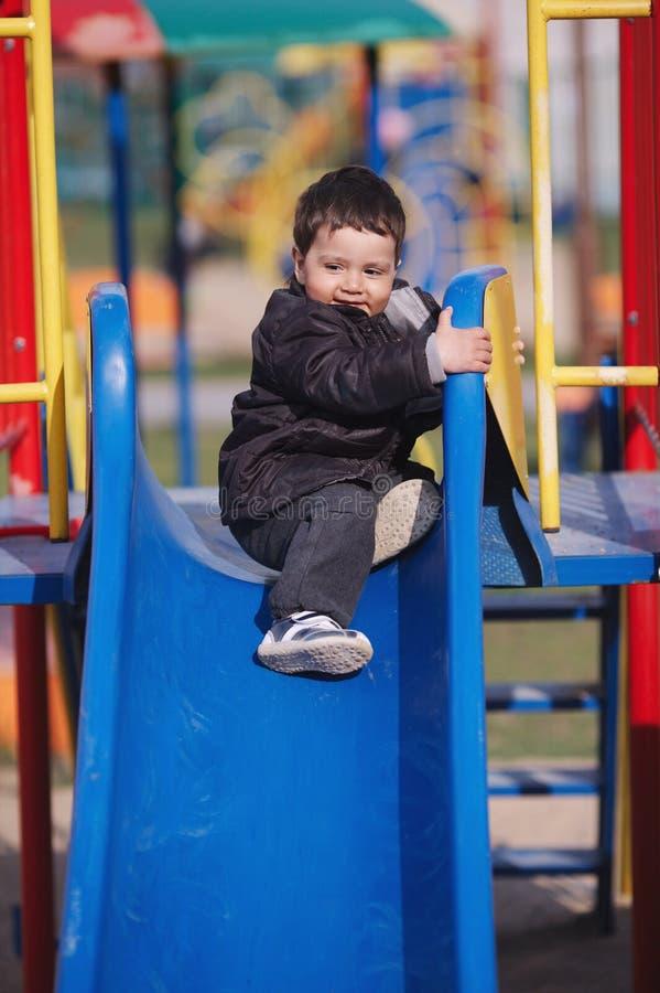 мальчик немногая играя скольжение стоковая фотография