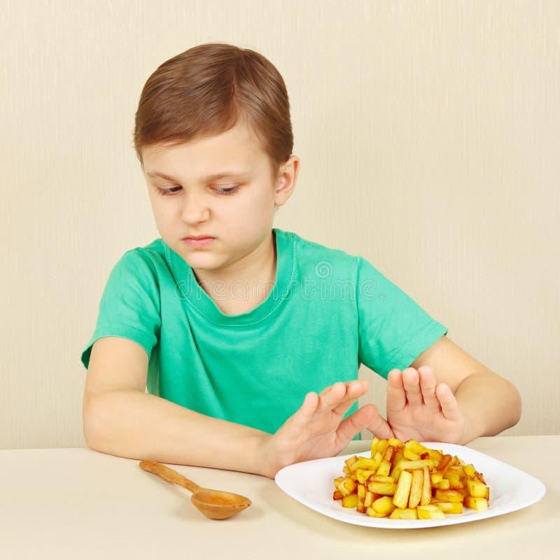Мальчик не хочет съесть зажаренные картошки стоковые изображения rf