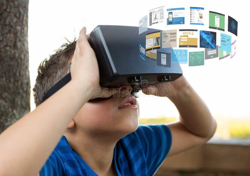Мальчик нося шлемофон виртуальной реальности VR с интерфейсом стоковые изображения