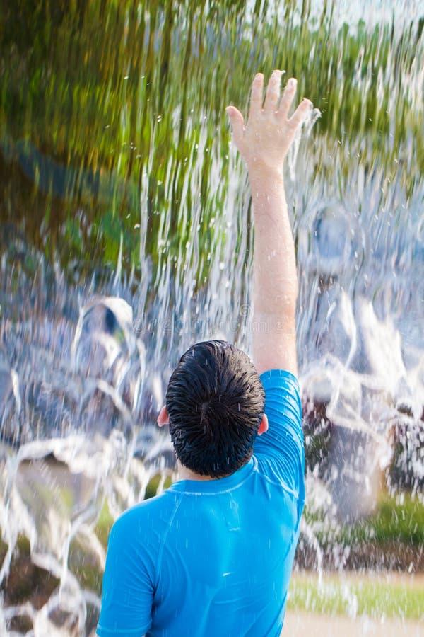 Мальчик достигая до воды чувства в водопаде стоковые фото
