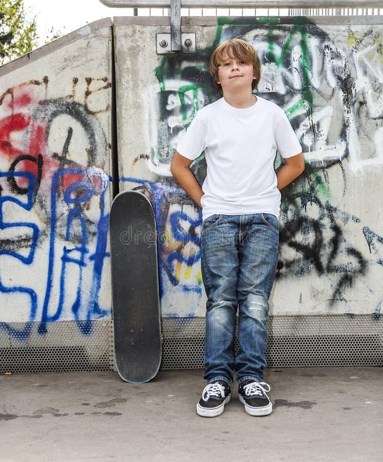 Мальчик ослабляет с его доской конька на парке конька стоковые изображения rf