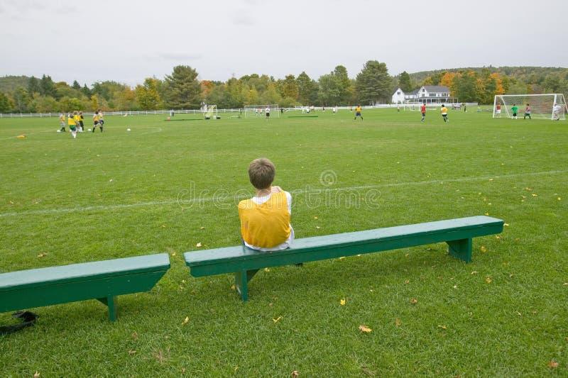 Мальчик отдыхает на стенде во время практики футбола школы, Нью-Гэмпшир стоковое изображение rf