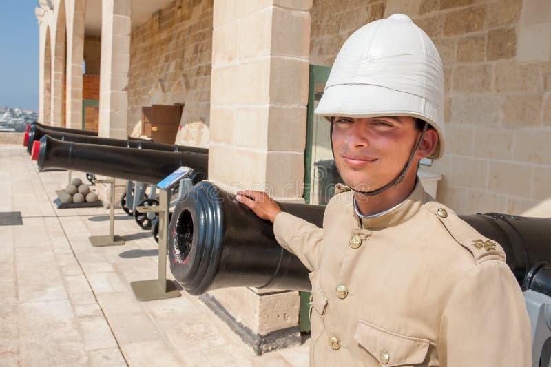 Мальчик одетый как в старой английской военной форме перед карамболями в Валлетте, Мальте стоковые фото