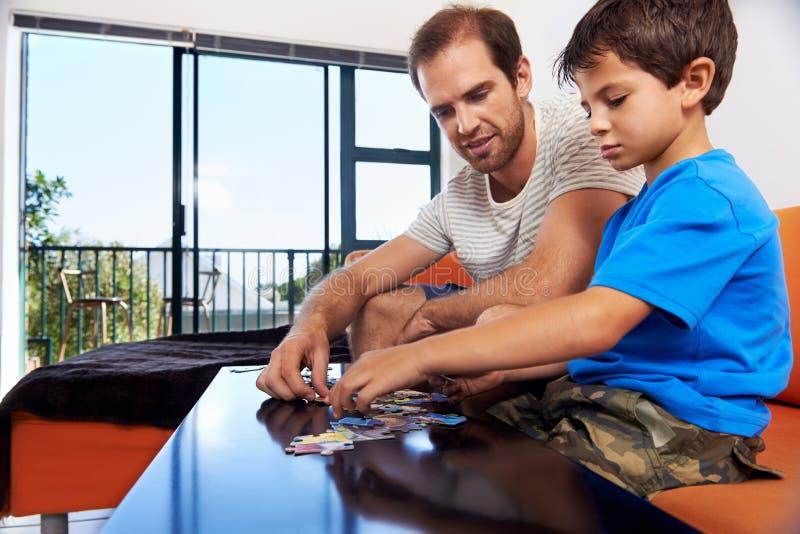 Мальчик папы головоломки стоковое изображение