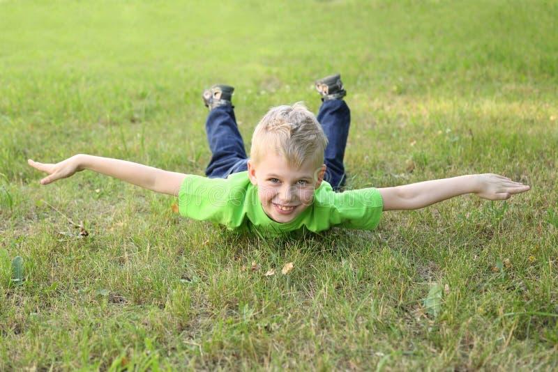 Мальчик показывает самолет на траве стоковые фотографии rf