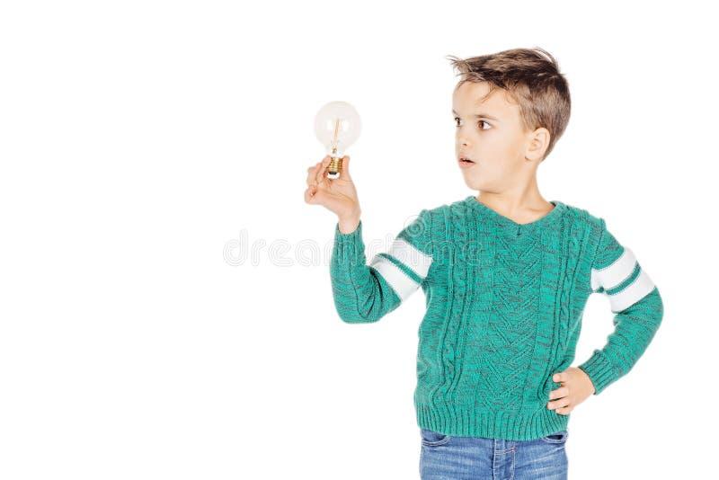 Мальчик портрета молодой счастливый держа лампочку изолированный на белизне стоковая фотография
