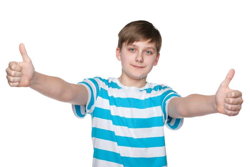 Мальчик подростка держит его большие пальцы руки вверх стоковые изображения rf
