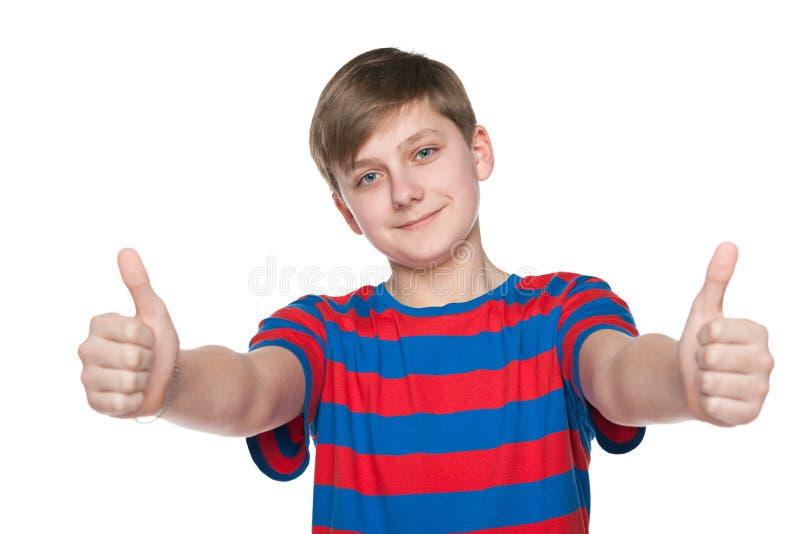 Мальчик подростка держит его большие пальцы руки вверх стоковая фотография
