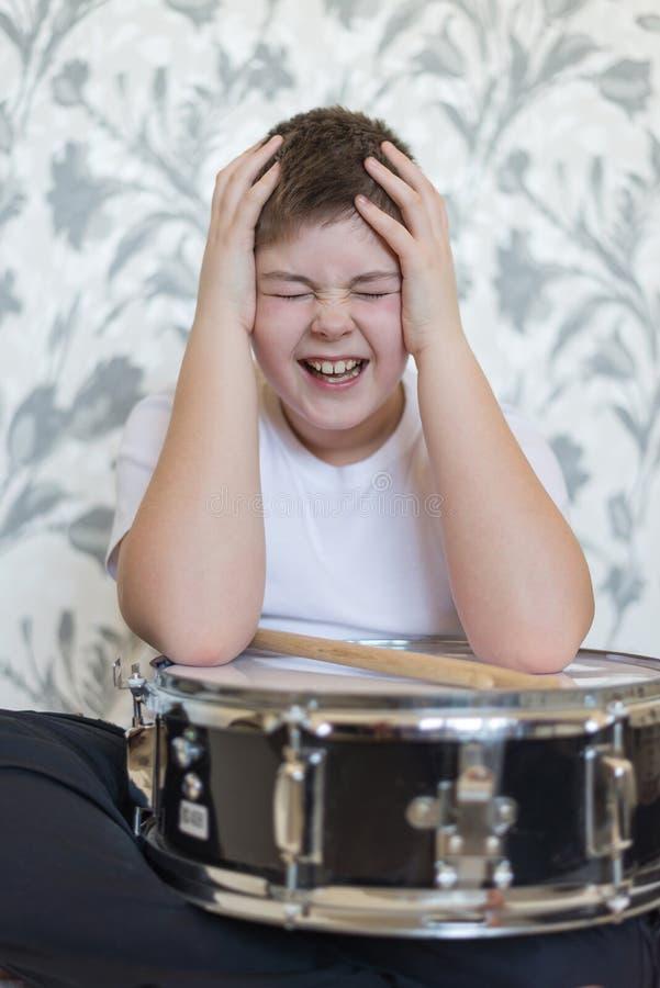 Мальчик подростка при барабанчик держа его голову стоковая фотография rf