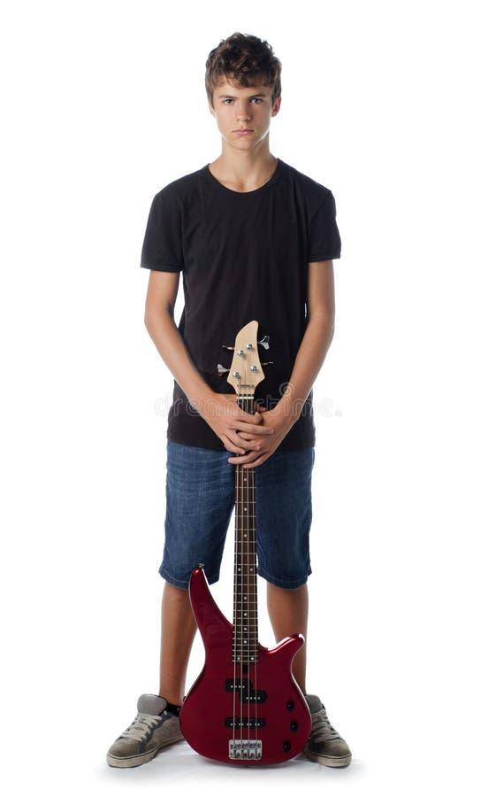 Мальчик подростка с басовой гитарой серьезной стоковое фото rf