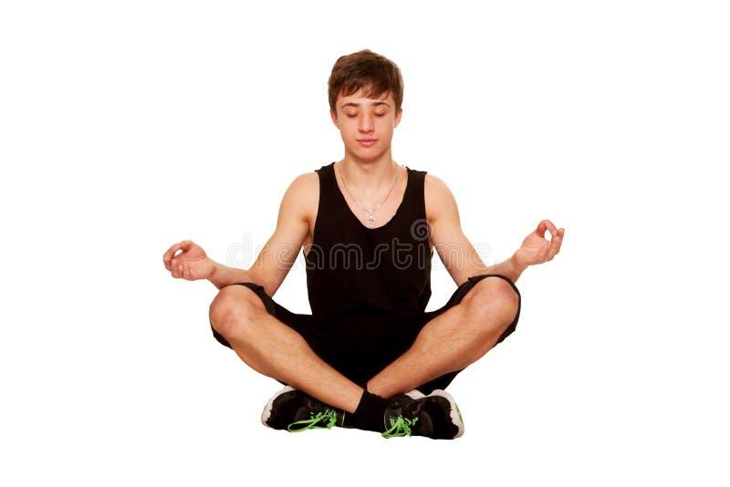 Мальчик подростка meditating и ослабляя после разминки. стоковая фотография