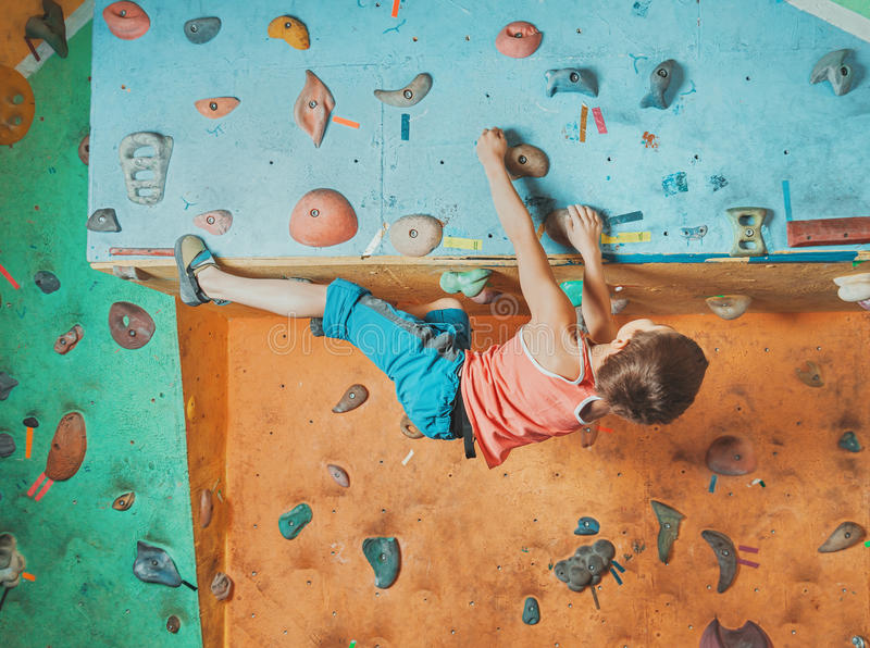 Мальчик практикуя в взбираясь спортзале стоковые фото