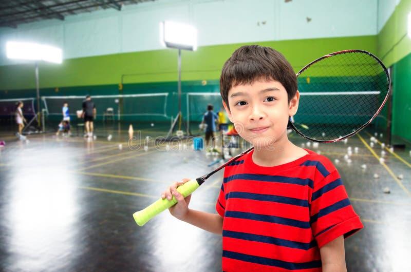 Мальчик принимая ракетку бадминтона в учебном классе стоковое изображение