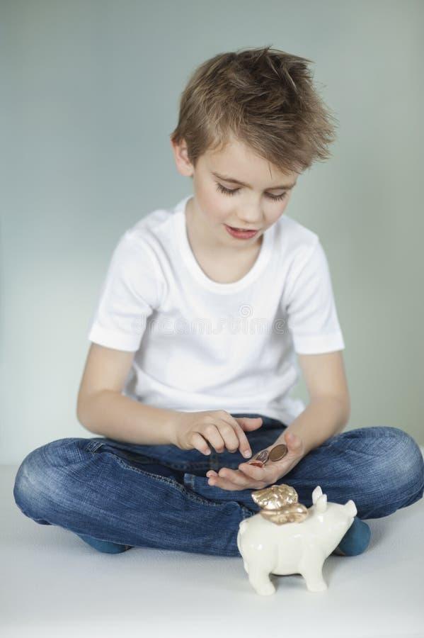 Мальчик при копилка подсчитывая монетки над серой предпосылкой стоковая фотография