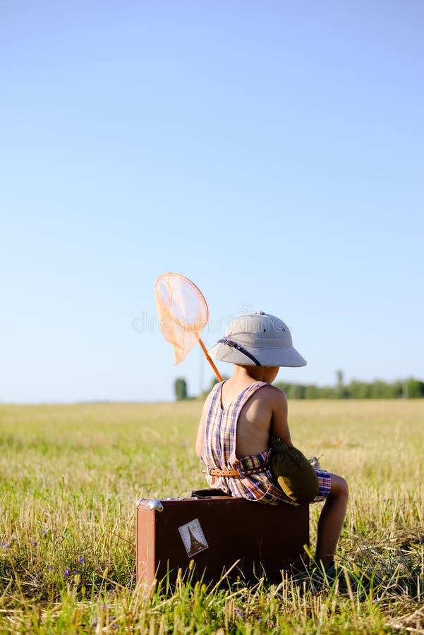 Мальчик при кольц-сеть сидя на чемодане внутри стоковые фотографии rf