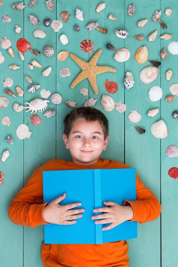 Мальчик при пустая книга кладя вниз с близко раковин моря стоковая фотография rf