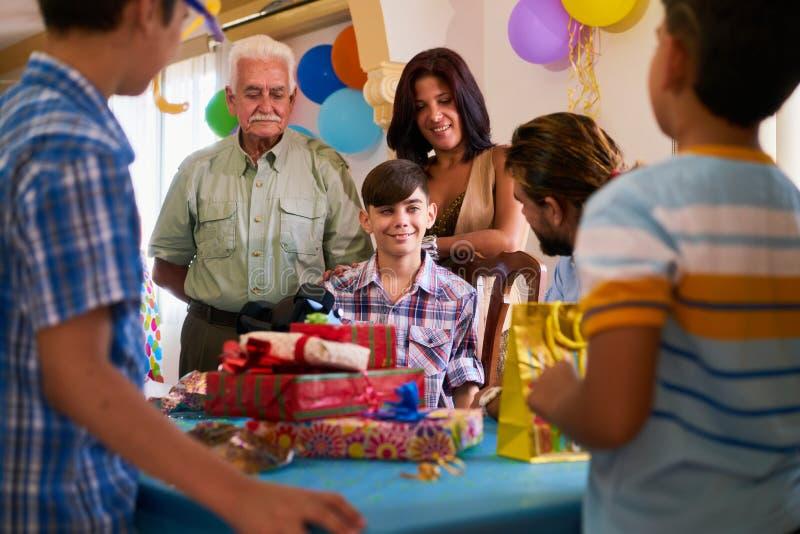 Мальчик при семья и друзья празднуя вечеринку по случаю дня рождения стоковая фотография rf