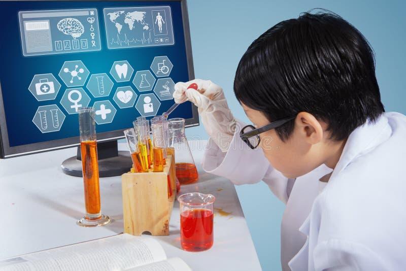 Мальчик проводя исследование исследование химии на столе стоковое фото rf