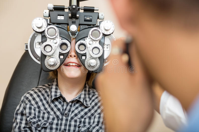 Мальчик проходя испытание глаза с Phoropter стоковые фото