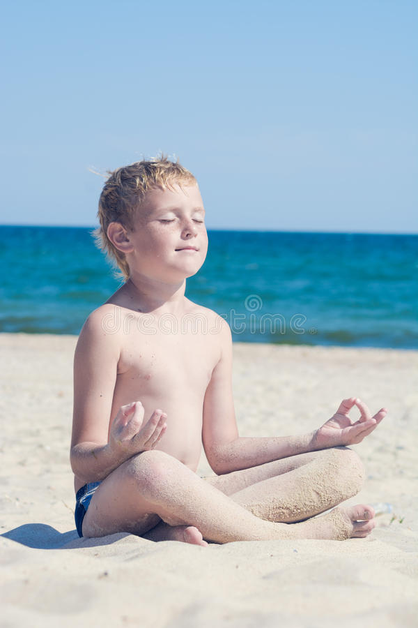 Мальчик размышляя на пляже около моря стоковые фото