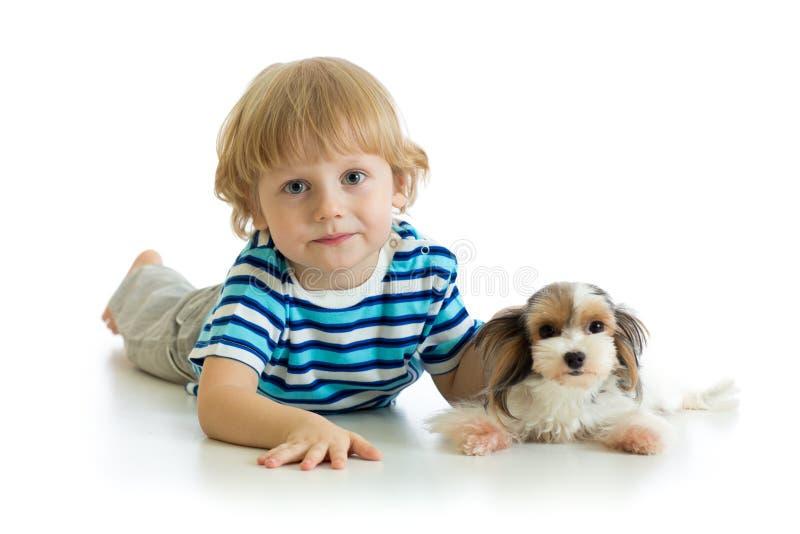 Мальчик ребенка и собака щенка смотря камеру изолированную на белой предпосылке стоковые фото