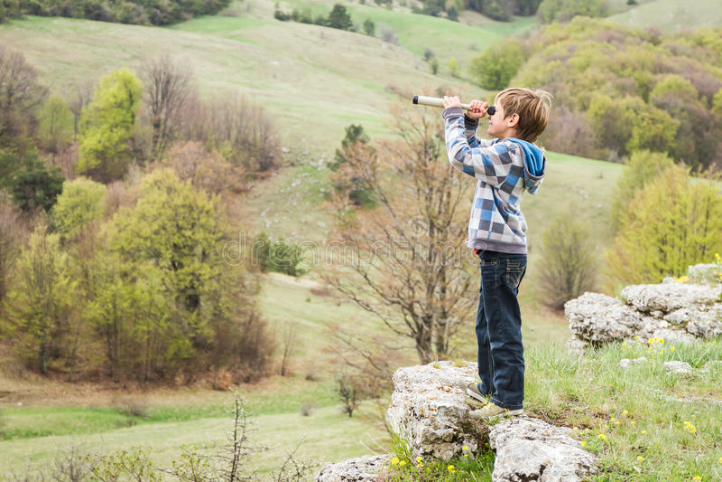 Мальчик ребенка смотря через бинокулярное к стороне страны стоковое изображение