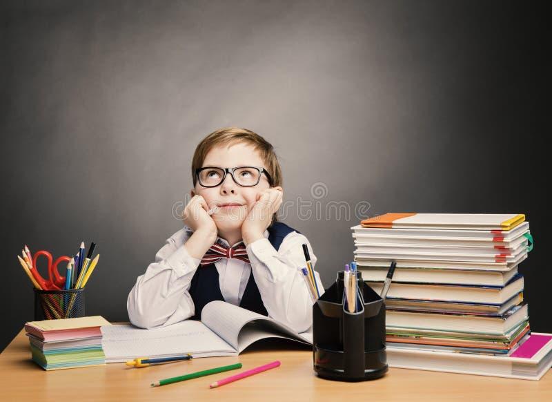 Мальчик ребенка школьного возраста в стеклах думает класс, книга студентов ребенк