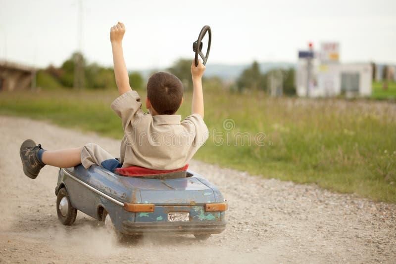 Мальчик ребенк управляя большим винтажным автомобилем игрушки с плюшевым медвежонком стоковое изображение rf