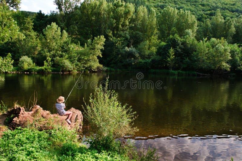 Мальчик рыболовства рекой стоковое фото