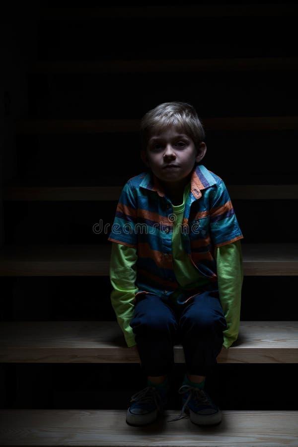 Мальчик самостоятельно на лестницах на ноче стоковое фото