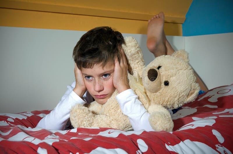 Мальчик сердитый на кровати стоковое фото rf