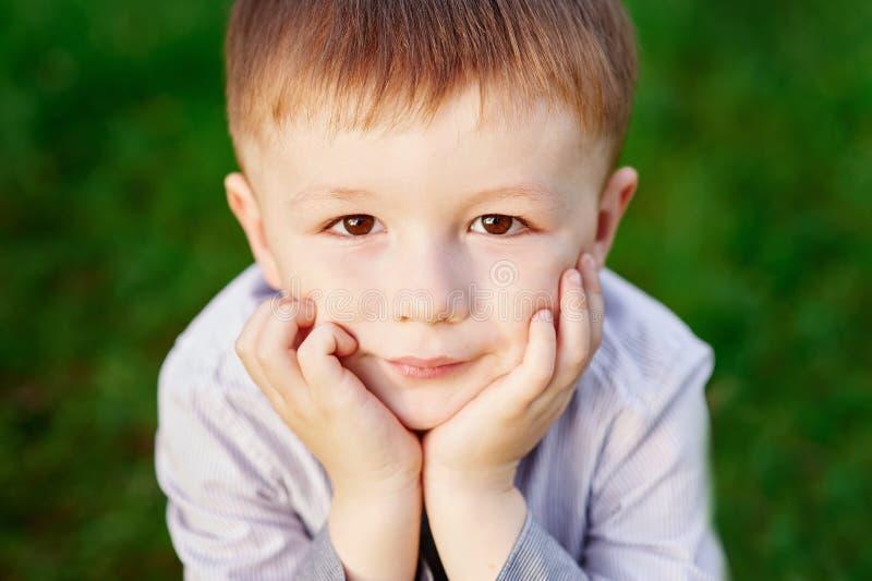 Мальчик сидит на зеленой траве в конце парка лета вверх стоковое фото