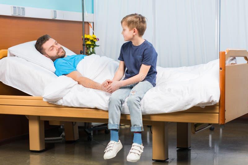 Мальчик сидя на больничной койке и смотря больного отца стоковая фотография