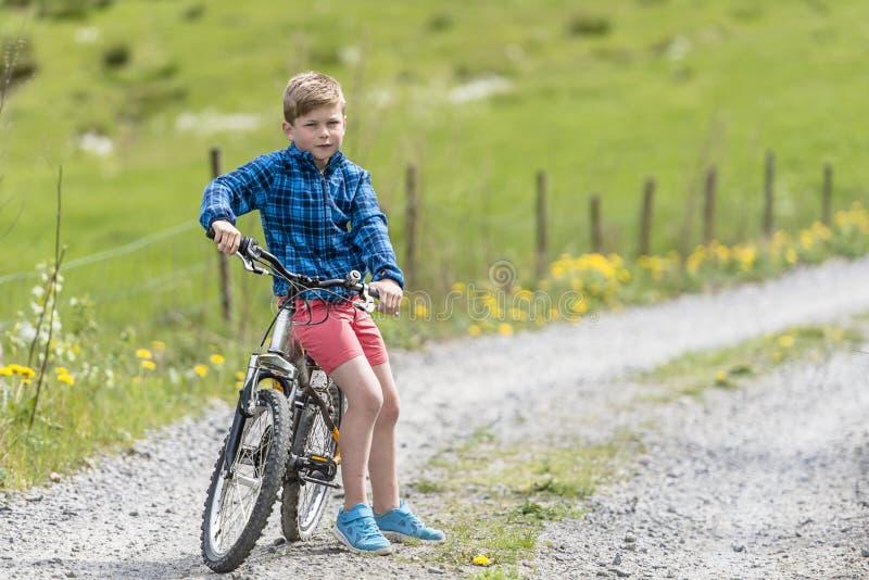 Мальчик сидя на его велосипеде стоковое фото