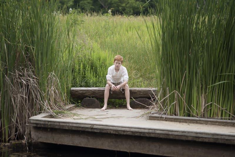 Мальчик сидя на журнале около высокорослой травы на озере стоковая фотография