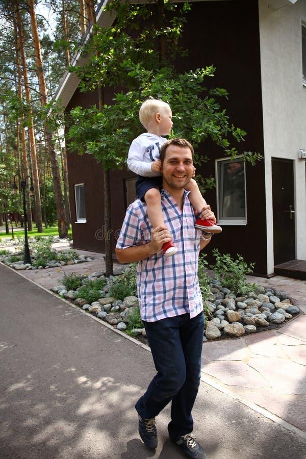 Мальчик сидя на плечах молодого отца стоковое фото rf