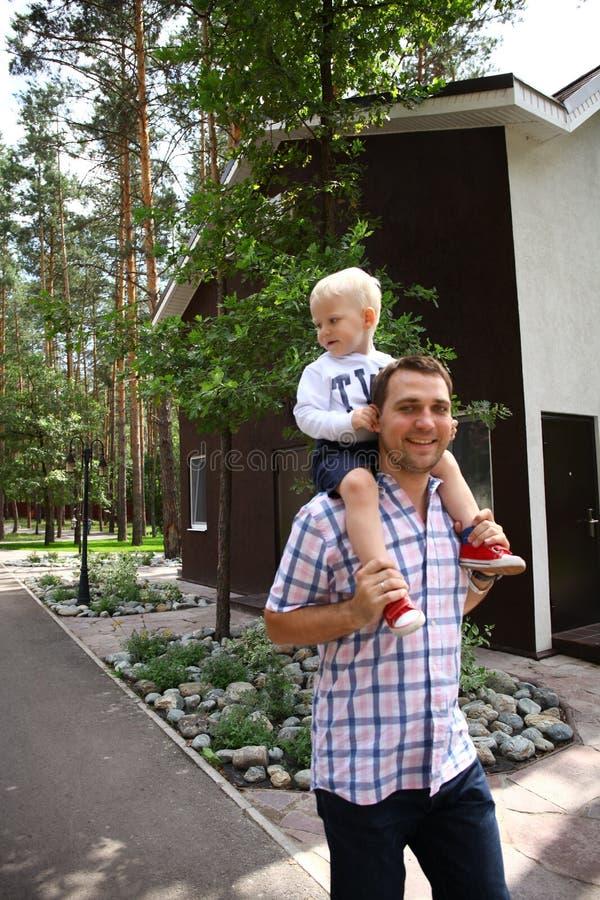 Мальчик сидя на плечах молодого отца стоковое изображение