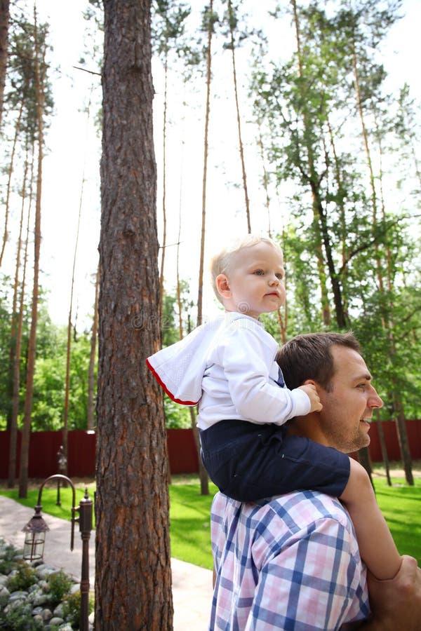 Мальчик сидя на плечах молодого отца стоковые изображения rf