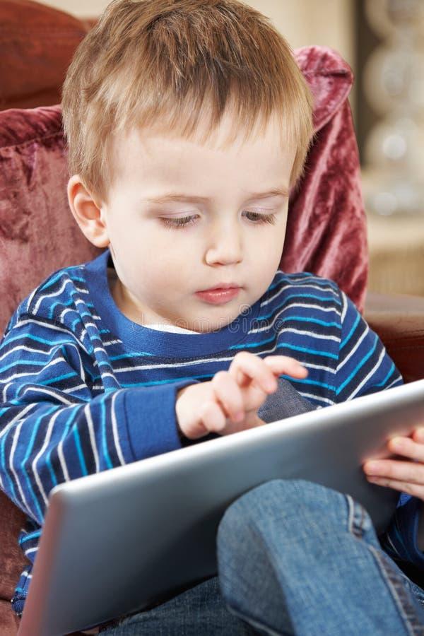 Мальчик сидя на софе и играя с таблеткой цифров стоковое фото