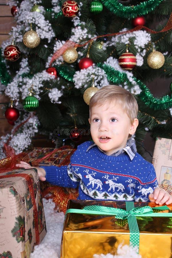 Мальчик сидя под рождественской елкой стоковая фотография