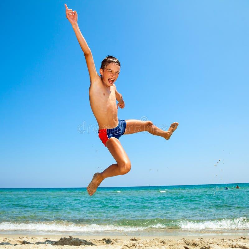 Мальчик скача на пляж стоковые фотографии rf