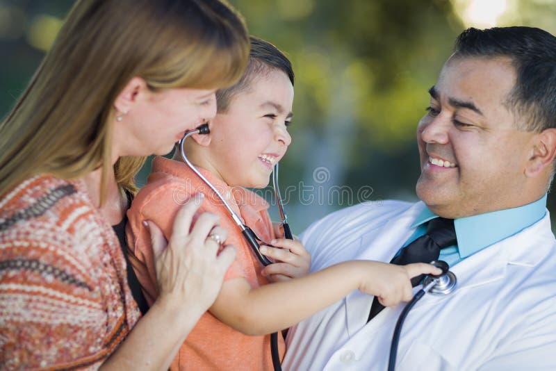Мальчик смешанной гонки, мать и доктор Иметь Потеха С Стетоскоп стоковое изображение