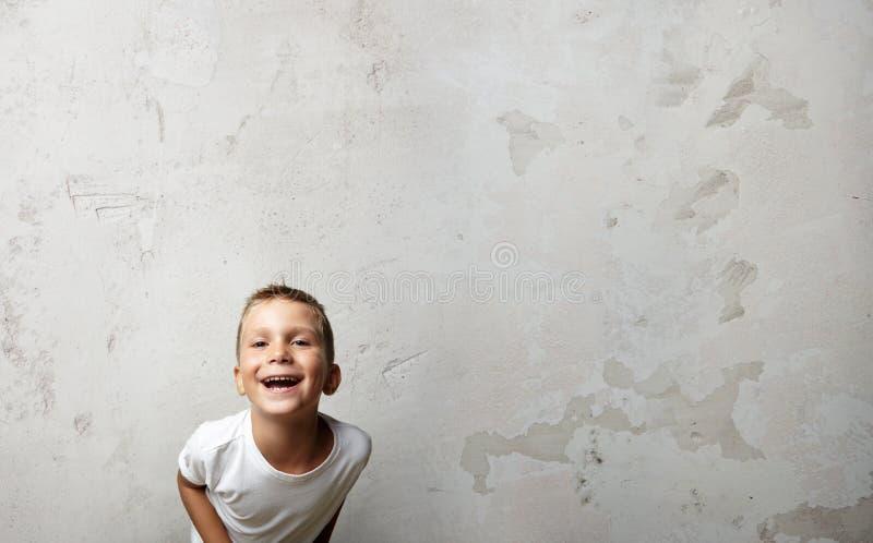Мальчик смеясь над на камере Стена Cocrete дальше стоковое изображение rf