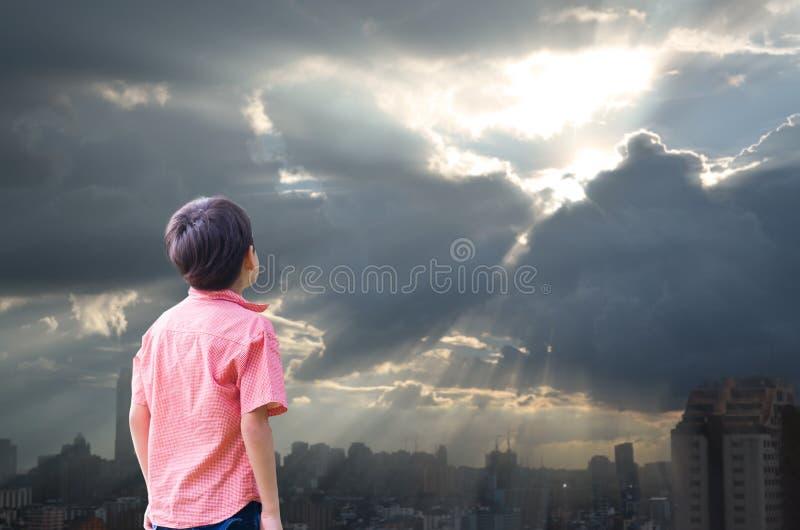 Мальчик смотрит вверх высоким в солнце неба с пасмурным стоковая фотография rf