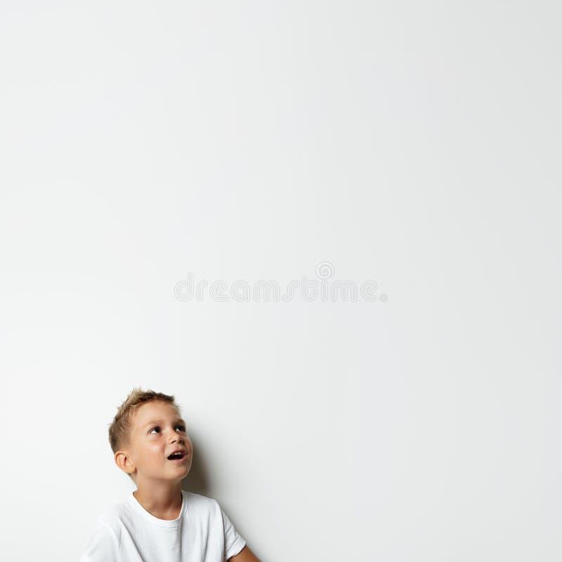 Мальчик смотря в сюрпризе вверх и усмехаться стоковые фото