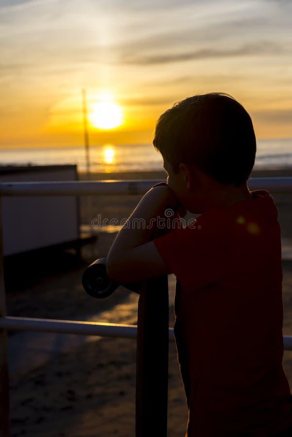 Мальчик смотря заход солнца стоковое изображение rf
