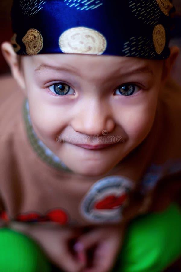 Мальчик смотря камеру, голубые глазы яркие в bandana стоковое фото rf