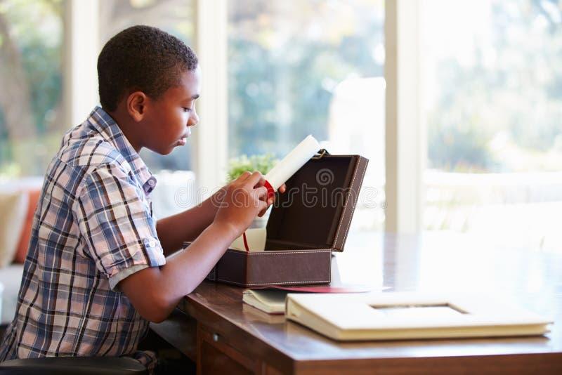 Мальчик смотря документ в коробке Keepsake на столе стоковое фото