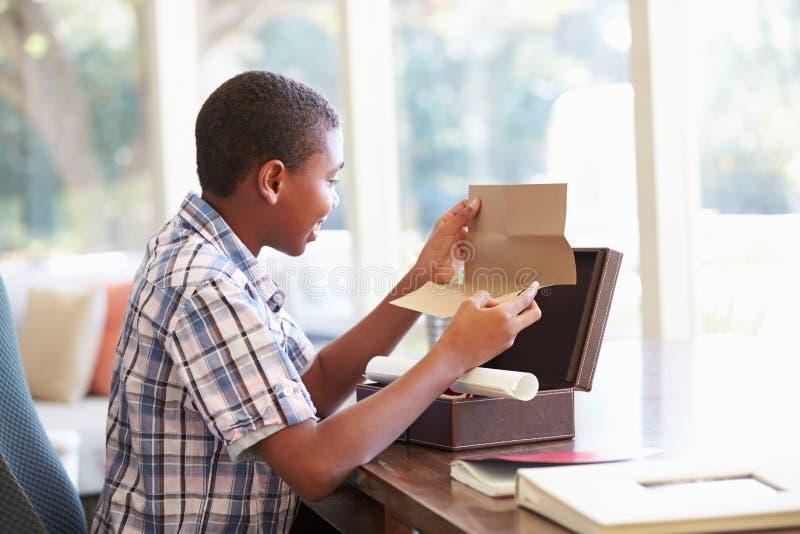 Мальчик смотря письмо в коробке Keepsake на столе стоковая фотография rf