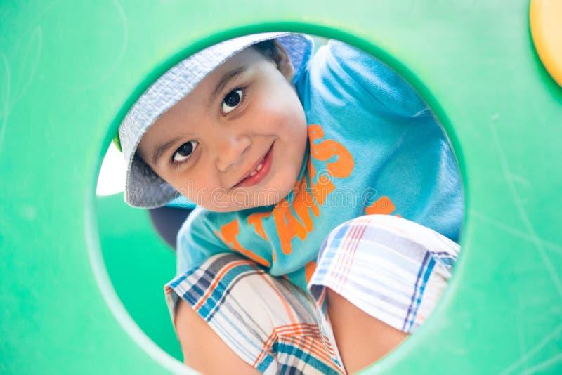 Мальчик смотря через круглое отверстие стоковая фотография